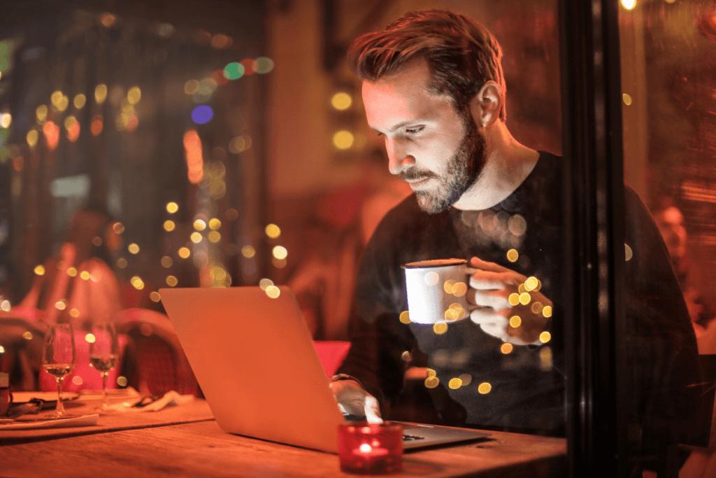 man holding mug in front of laptop 842548 min
